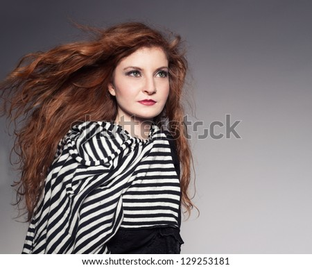 young ginger model wearing a black and white scarf posing in studio on grey background