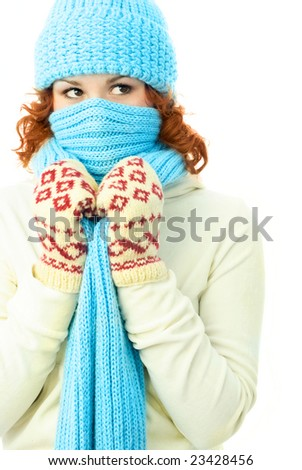 young ginger woman wearing warm winter clothes and hiding from the frost