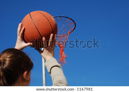Young girl about to try and score at basketball against a blue sky background.
