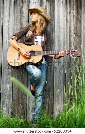 Young girl against a wooden wall playing guitar