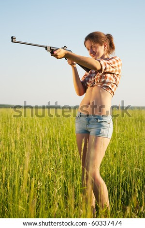 young girl aiming pneumatic air rifle outdoor