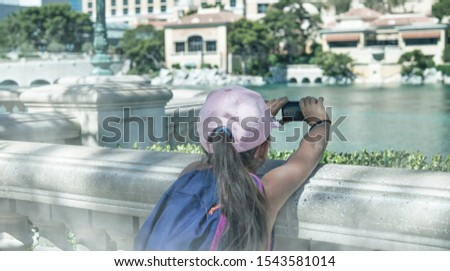Young girl amazed by Las Vegas Trip attractions, making pictures with small camera, back view. Travel, holiday and vacation concept