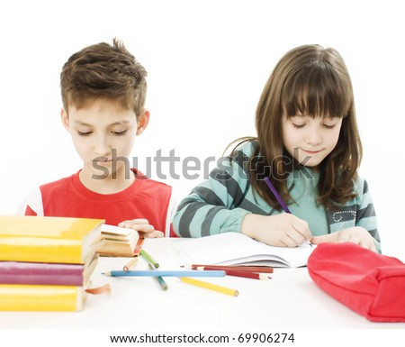Young girl and boy doing their homework  on the desk. Isolated on white - stock photo
