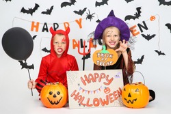 Young girl and boy in costumes with pumpkin buckets and text Happy Halloween