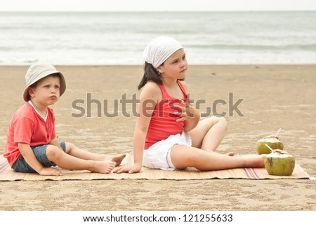 Young girl and boy with coconut on beach