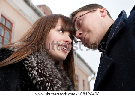 Young girl and guy look at each other, in the winter, in the city. Blurred roof houses in the background.