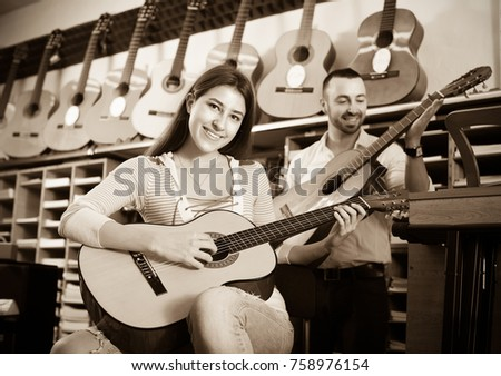 Young girl and handsome guy playing the guitars in shop