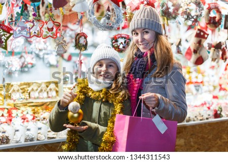 Young girl and her mother are demonstraiting decorations for Christmas tree in the market outdoor.