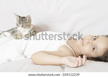 Young girl and kitten laying down on a white sofa.