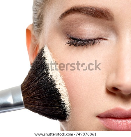 Young girl applies  powder  on the face using makeup brush.