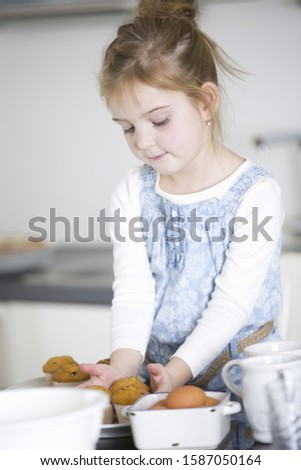 Young girl arranging cupcakes in kitchen