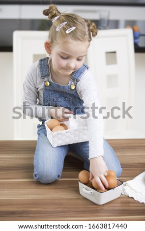 Young girl arranging eggs in kitchen