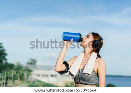 Shutterstock Young girl asian drinking protein shake nutrition and listen music after exercise running workout outdoor at beach seaside in summer for muscle building and slim fit body nice strong perfect.