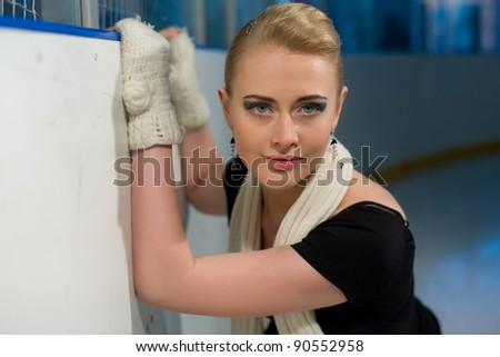 Young girl at a side of ice rink