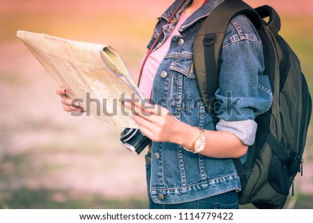 Young girl backpack tourist hand holding a map for search and plan her tour.Woman traveler touring in the summer. #1114779422