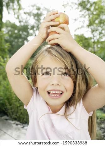 Young girl balancing apples on head