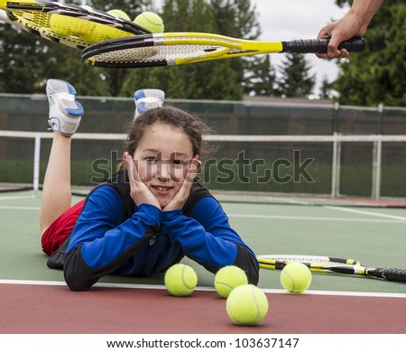 Young girl being given acceptance into tennis group with rackets over her head