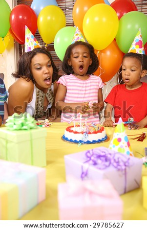 Young girl blowing out birthday candles with help from mother and brother