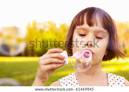 young girl blowing soap bubbles in a natural outdoor
