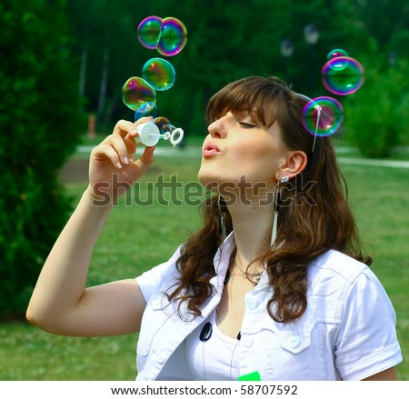 Young girl blowing soap bubbles in autumn park