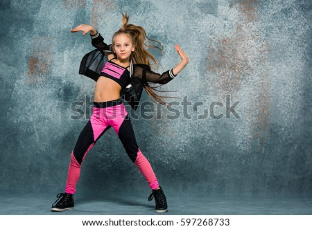 Young girl break dancing on wall background. #597268733
