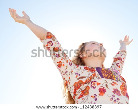 Young girl breathing fresh air with her arms raised  against a blue sky.