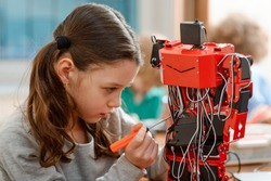 Young girl building a robot. Concentrated look on details and accurate work with a screwdriver. Engineering for beginners.