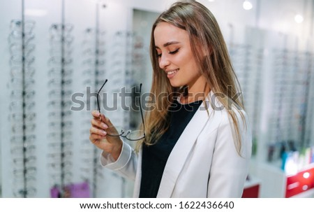 Young girl buys glasses. Stand with spectacles. Eyesight correction.