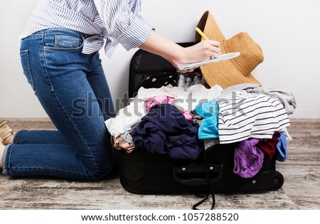 Young girl casually packs black suitcase