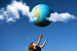 Young girl catches planet Earth. Happy child with globe in raised hands on blue sky background. Environment and ecology protection concept. World Earth Day greeting card, postcard idea
