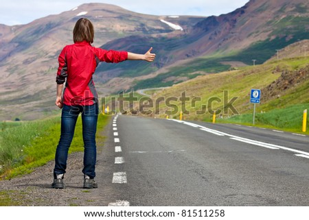 Young girl catching a car on empty road