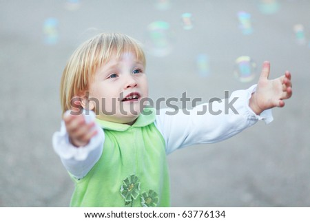 Young girl catching the soap bubbles