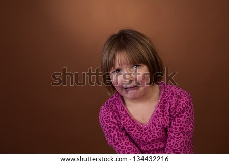 young girl caught eating blueberries with messy face. Part of a series