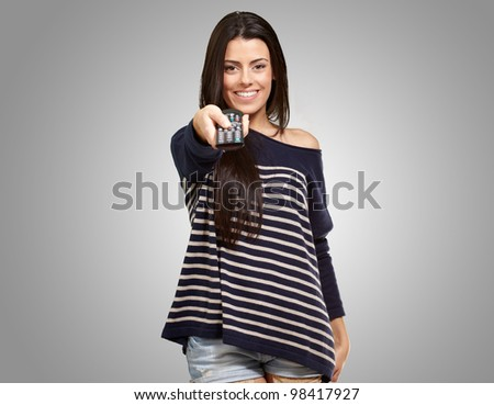 young girl changing channel over a grey background
