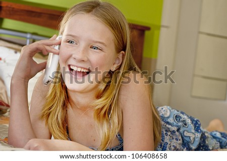 young girl chatting on a mobile phone, lying on her bed