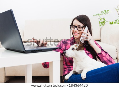 Young girl chatting on mobile phone, using computer  with pet dog in lap
