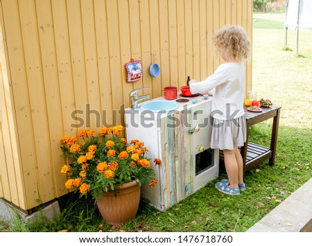 Young girl child playing outdoors in so called mud kitchen, where you can make fake food, play with sand, dirt, water, plants and make a mess, it develops imagination and exploration. #1476718760