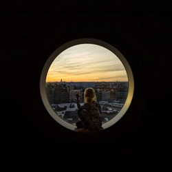 Young girl contemplating by looking through a round window during golden hour sunset.