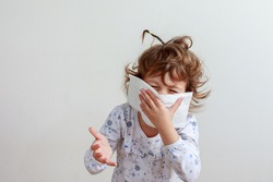 Young girl coughing into a paper handkerchief trying to say something in front of a white background