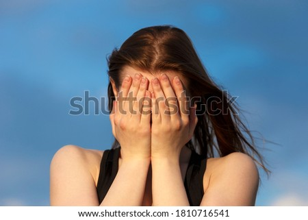 Young girl covering face with hands while crying. Depression concept.