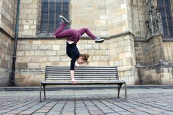 Young girl dancing breakdance in the square on the bench