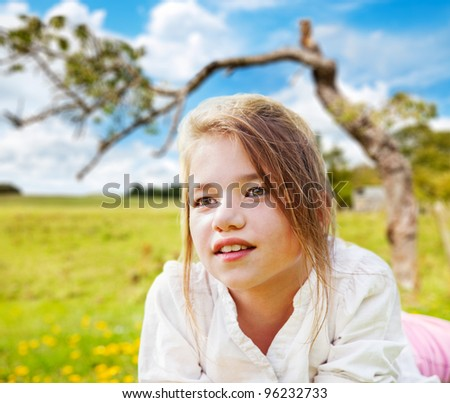 Young girl daydreaming in a sunny field