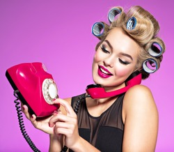 Young girl dials a phone number on an old phone. Young happy woman with blue curlers calling by retro phone.  Portrain of an atractive female using a vintage phone.