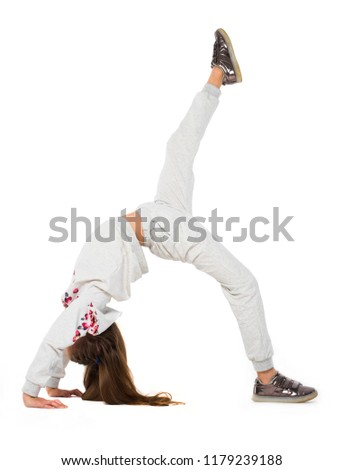 Young girl doing bridge position on the one leg support, one leg extended upwards