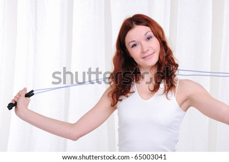Young girl doing exercises with skipping rope