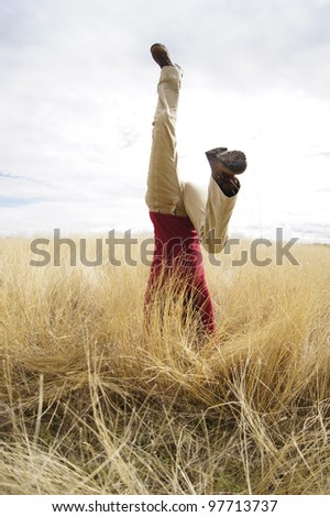 Young girl doing headstand in a filed of long grass