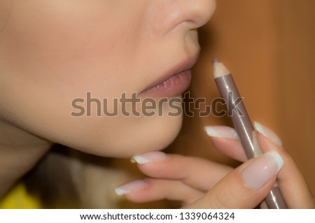 Young girl doing makeup contours the lips with a pencil #1339064324