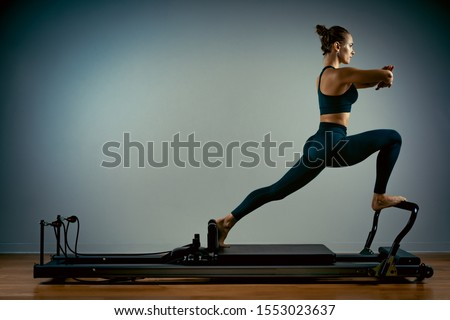 Young girl doing pilates exercises with a reformer bed. Beautiful slim fitness trainer on a reformer gray background, low key, art light, copy space advertising banner Stockfoto ©