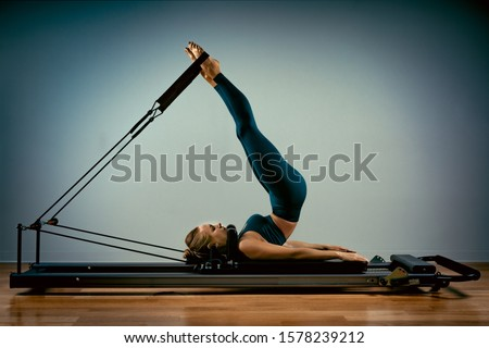 Young girl doing pilates exercises with a reformer bed. Beautiful slim fitness trainer on reformer gray background, low key, art light. Fitness concept Stockfoto ©