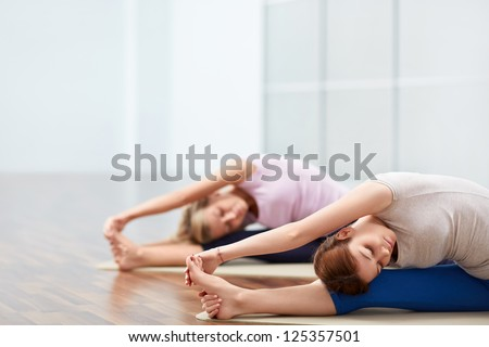 Young girl doing stretching indoors